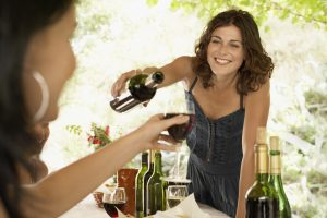 Woman Pouring Wine at Dinner Party - insomnia