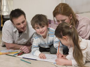 Parents on Floor Coloring With Children - planning your homeschooling curriculum