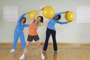 Women Using Exercise Balls in Fitness Class - brain health