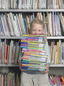 Elementary Student Reading in Library - planning your homeschooling curriculum