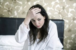 woman with headache - problem with oversleeping